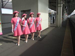 新幹線の乗客に手を振るミスピーチキャンペーンクルー